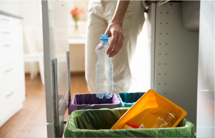 Recykling śmieci - butelka plastikowa wyrzucana do odpowiedniego pojemnika